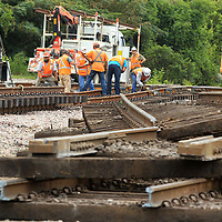 A BNSF work crew works on the rails at Spring Street behind the Tupelo Farmers Depot on Monday replacing sections of old rails.