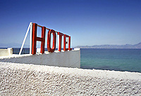 A hotel sign atop a roof in Kokkoni Beach, Greece.