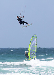 © Licensed to London News Pictures. 27/06/2020. Newquay, UK. A kitesurfer performs a jump as a windsurfer passes nearby, during windy weather at Watergate Bay, Cornwall. The weather is variable with sunny outbreaks and rainy showers. Photo credit : Tom Nicholson/LNP