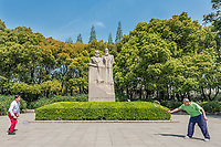 Shanghai, China - April 7, 2013: two people exercising badminton in front of marx and engels statue in fuxing park at the city of Shanghai in China on april 7th, 2013