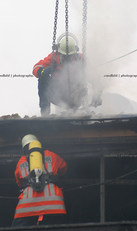 Zwei Feuerwehrmänner versuchen eine Kette an einem brennenden Fabrikhallendach zu befestigen...German Fire Fighters at a burning industrial complex in Dannenberg.