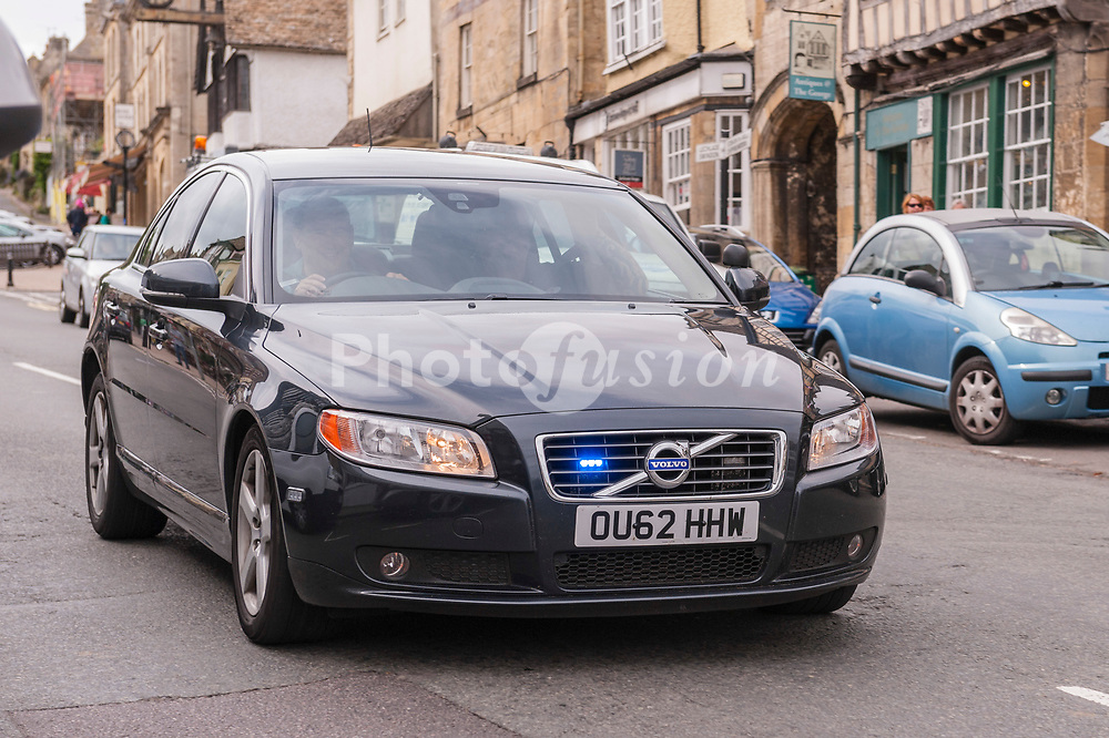 An unmarked police car flashes its blue lights as it speeds through Burford , Oxfordshire , England , Britain , Uk
