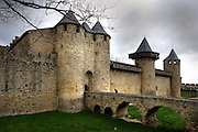 East side of the Castle with gateway of a semicircular barbican, Citadel of Carcassonne, Aude, France, pictured on February 24, 2007, on a cloudy winter afternoon. The two outer walls of the concentric fortified city are defended by towers and barbicans, and a draw bridge across a moat leads to the keep of the castle. Carcassonne was a stronghold of Occitan Cathars during the Albigensian Crusades but was captured by Simon de Montfort in 1209. He added extra fortifications and Carcassonne became a citadel on the French border with Aragon. The fortress restored in 1853 by Eugene Viollet-le-Duc. Today it is a UNESCO World Heritage site. Picture by Manuel Cohen.