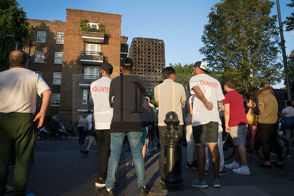 © Licensed to London News Pictures. 16/06/2017. London, UK. Volunteers stand in evening sunshine as they look at the  burnt remains of Grenfell Tower. The blaze engulfed the 27-storey building in the early hours of June 13th. Police say 30 people have been killed with 34 still in hospital, 18 of whom are in critical condition. The fire brigade say that they don't expect to find anyone else alive. Photo credit: Peter Macdiarmid/LNP