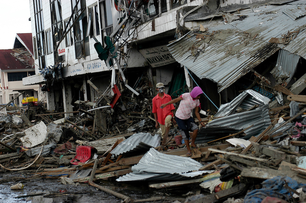 Locals move carefully through the debris of the Tsunami devstated city of Banda Aceh. January 2005