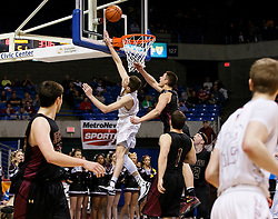 Wheeling Central guard Chase Harler (14) gets two points in a difficult shot at the rim during a semi final round game at the Charleston Civic Center.