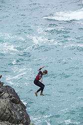 A teenager tombstoning off cliffs on The Headland in Newquay, Cornwall.