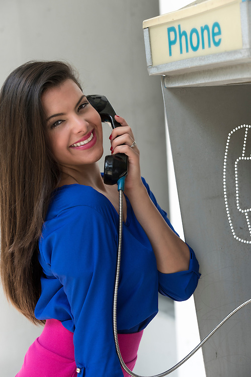 Young hispanic woman talking in a public phone