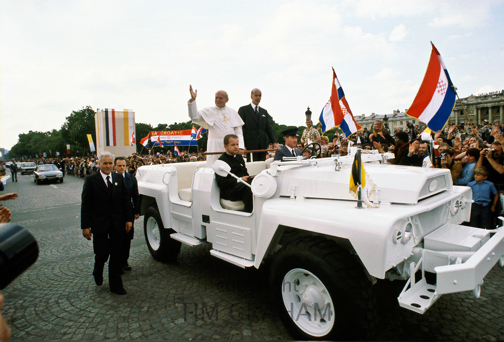 Pope John Paul II during his historic visit to Paris in 1980 travels in motorcade with light minimal security of open top car