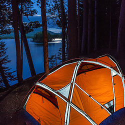 A tent in moonlight on Flagstaff Lake in Eustis, Maine. Bigelow Mountain is in the distance.
