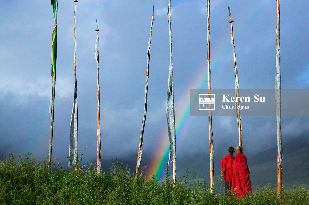 Rainbow over two monks with praying flags in the Phobjikha Valley, Gangtey village, Bhutan