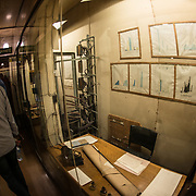 A cramped corridor used by officer's tracking the prorgess of the war at the Churchill War Rooms in London. The museum, one of five branches of the Imerial War Museums, preserves the World War II underground command bunker used by British Prime Minister Winston Churchill. Its cramped quarters were constructed from a converting a storage basement in the Treasury Building in Whitehall, London. Being underground, and under an unusually sturdy building, the Cabinet War Rooms were afforded some protection from the bombs falling above during the Blitz.