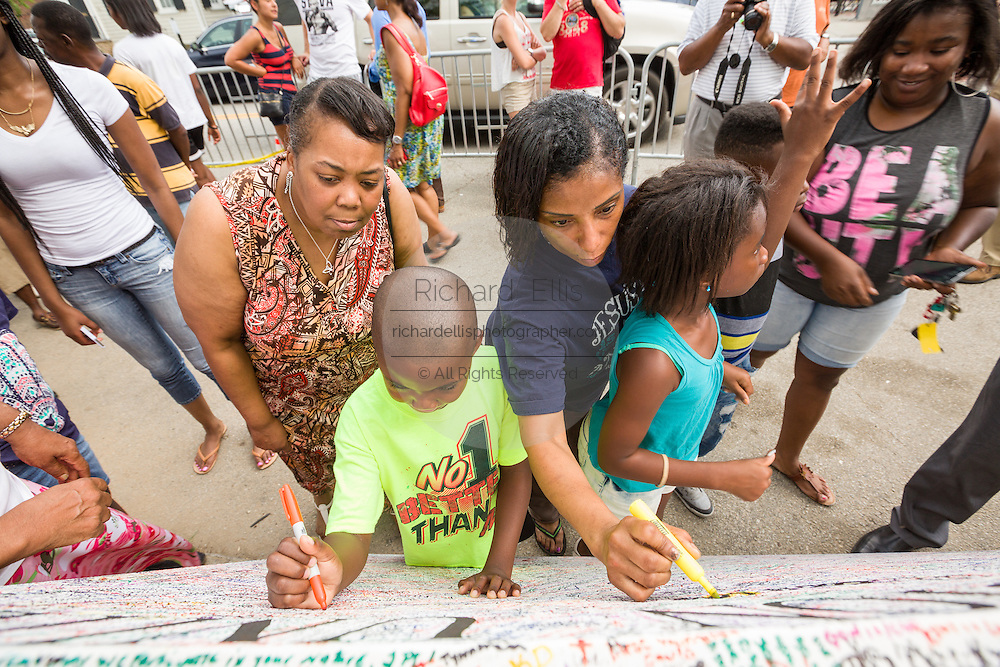 Residents write messages at a makeshift memorial outside the historic Mother Emanuel African Methodist Episcopal Church June 22, 2015 in Charleston, South Carolina. Nine people killed at the church by white supremacist, Dylann Storm Roof last Wednesday.