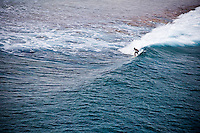 Local boy grabs a hollow wave in the Tuamotus, French Polynesia as it barrels into the pass.  I'm perched precariously at the top of our mast shooting some of the pro athletes we have on board and caught this shot.