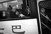 A man holds a child in his lap on a crowded bus in Chongqing.