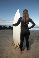 Female surfer standing holding surfboard on beach back view