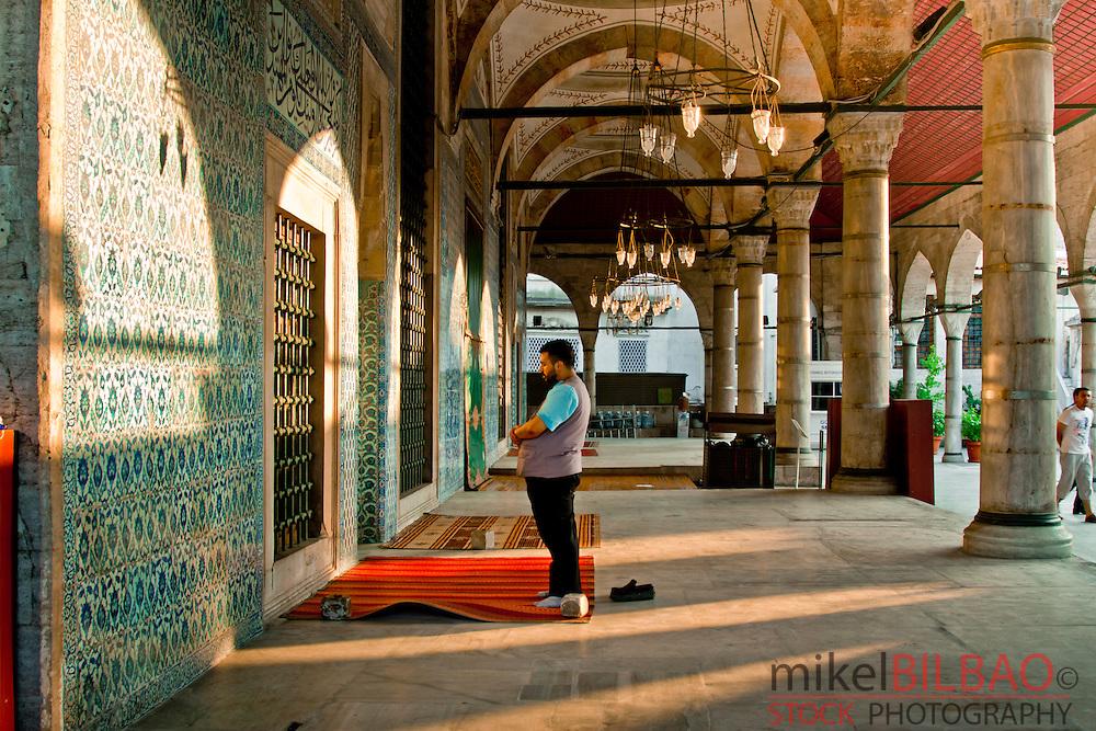 Man praying in Rustem Pasha Mosque.<br /> Istanbul, Turkey.