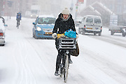 Een fietser rijdt door de sneeuw.<br /> <br /> A cyclist is riding in the snow