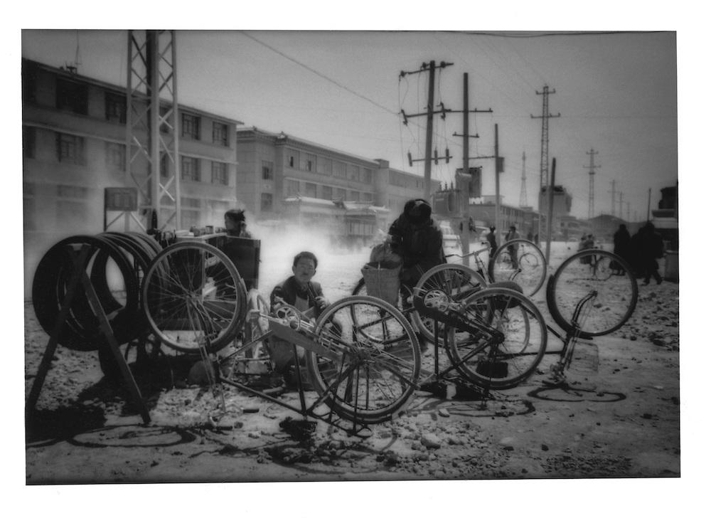 Bicycle repairman on the Chinese side of the Tibetan town of Zhongdian, Yunnan (Gyeltangteng, Kham), China.  1997
