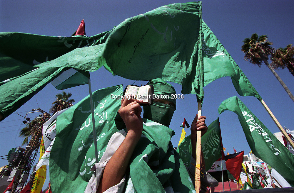A boy, carrying HAMAS flags and his faced covered in the colors of HAMAS, holds a small Koran book during a rally for the second anniversary of the Intifada in Gaza City. (Photo/Scott Dalton)