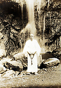 person with praying beads standing in front of waterfall