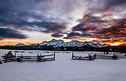Winter sunset with rail fence in foreground and Sawtooth Mnts in background