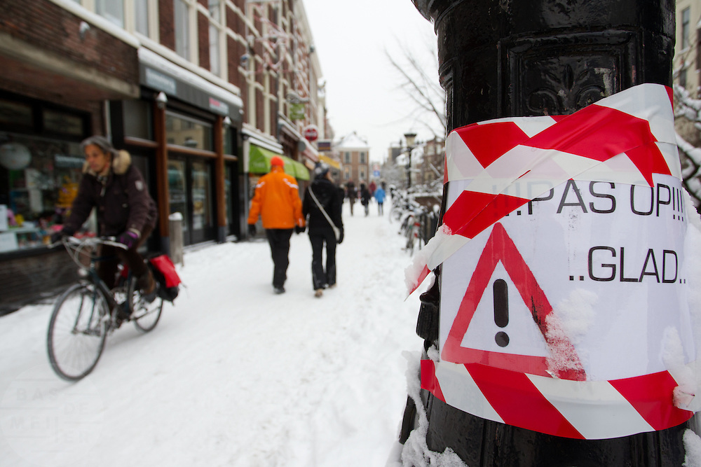 Een plakaat bij de Vismarkt in Utrecht waarschuwt voor gladheid. De hevige sneeuwval in Nederland heeft voor de nodige problemen gezorgd in het land.<br /> <br /> A sign at the Vismarkt in Utrecht is warning for slipperiness.