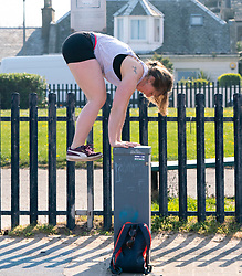 Portobello, Scotland, UK. 25 April 2020. Views of people outdoors on Saturday afternoon on the beach and promenade at Portobello, Edinburgh. Good weather has brought more people outdoors walking and cycling. The beach appears busy with possibly a breakdown in social distancing happening later in the afternoon. Woman exercising using street furniture on the promenade.  Iain Masterton/Alamy Live News
