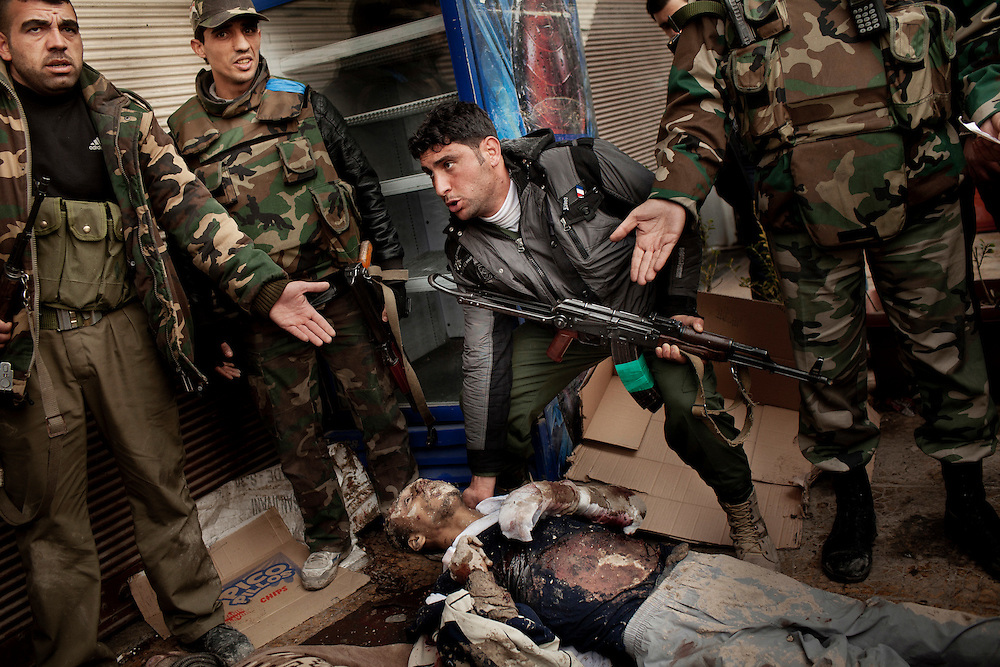 Syrian soldiers show to the Arab League Observers and the press the bodies of a civilian with marks of torture and a killed soldier (unseen) in Kafr Batna, in the outskirts of Damascus, Syria. January 26, 2012. Photo/Tomas Munita
