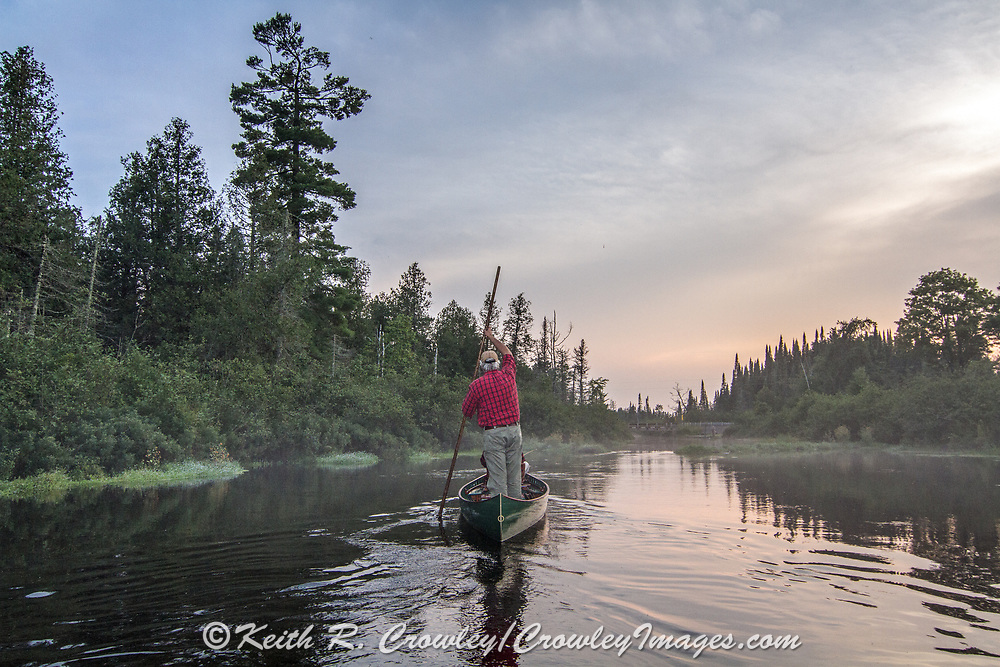 Brule River fishing guide Damian Wilmot poles upstream on the Brule near Lake Nebagamon, Wisconsin with angler Matson Holbrook in a 1895 Joe Lucius guide canoe Wilmot meticulously restored over the course of two years.