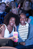 Young Couple sitting in theatre arms around Watching Movie eating popcorn