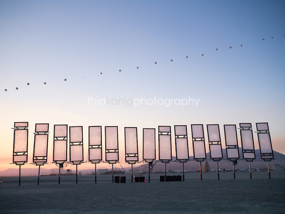 Performance balloon art floats above a solar art installation pre-dawn at Burning Man
