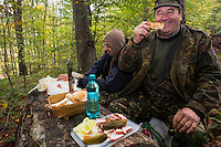 Romanian hunters having a snack in the forest after a driving hunt for Wild boar (Sus scrofa). Mehadia, Caras Severin, Romania.