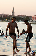 Badevergnügen in der Bucht vor Porec. Junge Männer spielen mit einem Fussball auf der Kaimauer. | Young men play soccer on a pier and try to shove each other into the water.