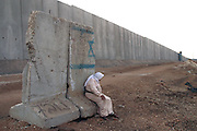 Palestinian woman Fatimya Baz,73, rests on a cement barrier with a painted Star of David by the 3 kilometer (1.8 mile) long concrete wall, sprung up along the northern West Bank town of Qalqiliya's western edge Oct.11,2002.  Israel says that the wall along with a electronic fence is necessary to stop Palestinian suicide bombers from slipping into Israeli towns and cities to carry out attacks. Fatimaya says that she can not even feel the wind anymore. Most of her farm land has been confiscated .The wall will separate thousands of Palestinians from their land and turn this town's 40,000 people into virtual prisoners, Palestinians and Israeli human rights activists charged. The barrier is expected to eventually run the full length of the 300-kilometer (180-mile) frontier between Israel and the West Bank, which it occupied in the 1967 Mideast war. (Photo by Heidi Levine/Sipa Press).