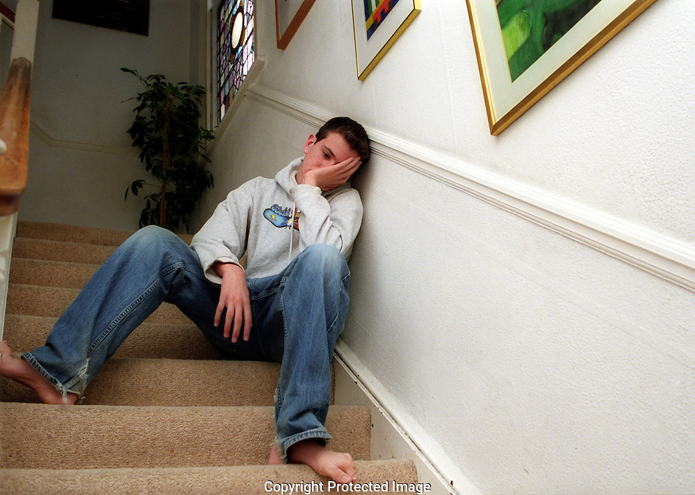 Depressed teenager sitting on hall steps.