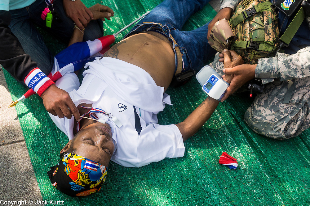"09 DECEMBER 2013 - BANGKOK, THAILAND:  Medics tend to an anti-government protestor who collapsed in the heat in front of Government House in Bangkok Monday. Thai Prime Minister Yingluck Shinawatra announced she would dissolve the lower house of the Parliament and call new elections in the face of ongoing anti-government protests in Bangkok. Hundreds of thousands of people flocked to Government House, the office of the Prime Minister, Monday to celebrate the collapse of the government after Yingluck made her announcement. Former Deputy Prime Minister Suthep Thaugsuban, the organizer of the protests, said the protests would continue until the ""Thaksin influence is uprooted from Thailand."" There were no reports of violence in the protests Monday.     PHOTO BY JACK KURTZ"