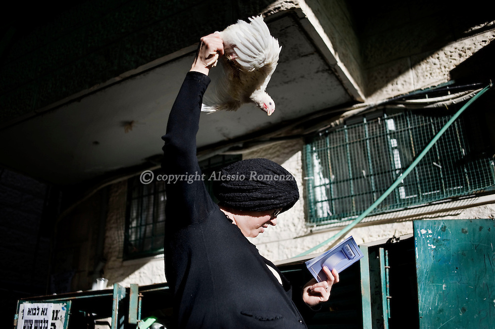 JERUSALEM : An Ultra-Orthodox Jewish woman swings a chicken over his head during the Kaparot ceremony in Mea Shearim neighborhood of Jerusalem on October 6, 2011. The Jewish ritual is supposed to transfer the sins of the past year to the chicken, and is performed before the Day of Atonement, or Yom Kippur, the most important day in the Jewish calendar, which this year will start on sunset on October 7. ALESSIO ROMENZI