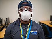 "19 MARCH 2020 - DES MOINES, IOWA:  SAM TEAH, a worker for the Des Moines Public Schools, wearing protective gear to clean a classroom at Central Campus, a high school in the Des Moines Public Schools system. Des Moines schools are closed for at least 30 days because of the coronavirus and officials are using the time to ""deep clean"" and sanitize each school. On Thursday morning, 19 March, Iowa reported 38 confirmed cases of the Coronavirus. Restaurants, bars, movie theaters, places that draw crowds are closed for at least 30 days. There are no ""shelter in place"" orders in effect anywhere in Iowa but people are being encouraged to practice ""social distancing"" and many businesses are requiring or encouraging employees to telecommute.        PHOTO BY JACK KURTZ"
