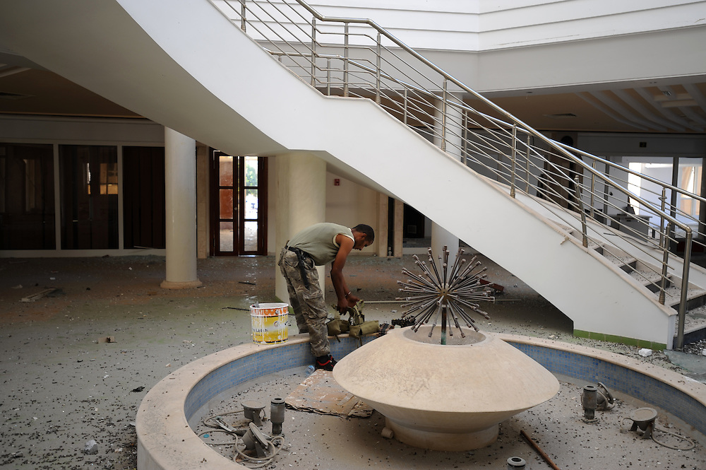 A rebel fighter reorganizes his gear in the semi-destroyed lobby of the Jewel Hotel in central  Zawiyah.