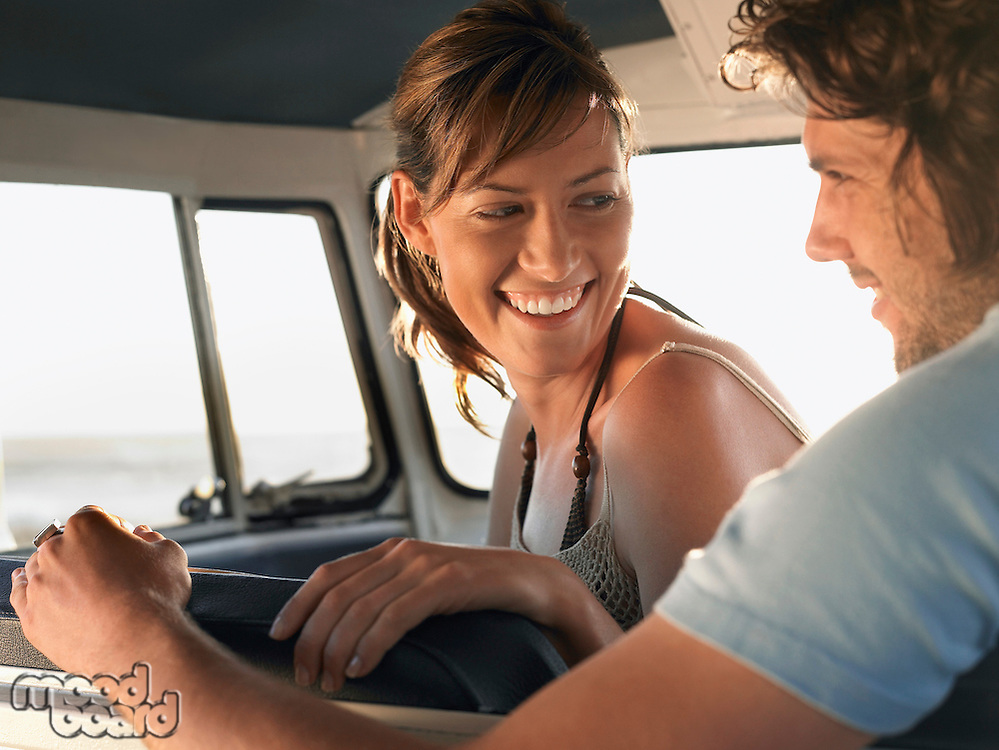 Young couple sitting in van head and shoulders