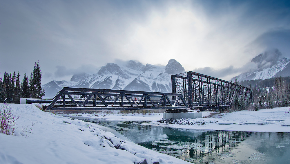 A man walks across Engine bridge during sunset in Canmore, Alberta on December 28th, 2015