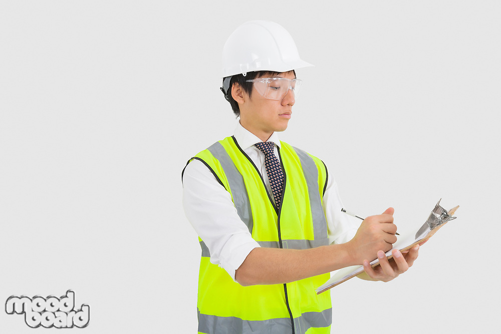 Man in reflector vest and hard hat writing on clipboard in office