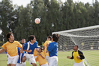 Soccer players jumping for ball