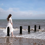 a woman in a white dress is sitting on a wooden pole in the sea