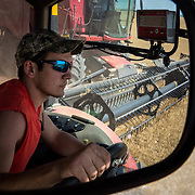 Alan Stoner, 21, drives a grain cart to collect harvested wheat from the combine reflected in his side view mirror. Crowell, TX, May 27, 2017.