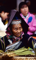 A woman wearing traditional ethnic minority dress attends to her market stall in Northern Vietnam.
