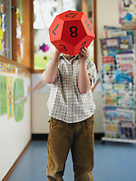 School Boy Playing with 12-Sided Die