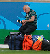 FA Chairman Greg Dyke sits reading a book with some packed bags during the England training session the day before their final Group D match against Costa Rica at Mineirão, Belo Horizonte, Brazil. <br /> Picture by Andrew Tobin/Focus Images Ltd +44 7710 761829<br /> 23/06/2014