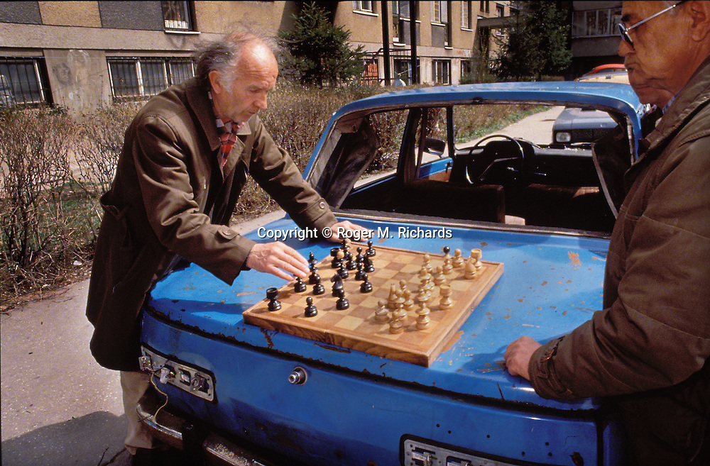 Men play a game of chess on the trunk of an abandoned car during the Bosnian Serb siege of Sarajevo, April 1993. Residents of the beleaguered city sought any escape or distraction from the reality of death and mayhem they faced every day. (Photo by Roger Richards)